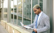 Businessman leaning against wall and reading newspaper — Stock Photo