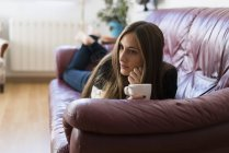 Frau liegt auf Couch mit Tasse Kaffee — Stockfoto