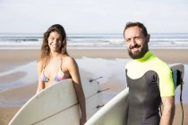Couple of surfers with surfboards at the seaside looking at camera — Stock Photo