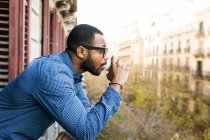 Портрет молодого человека, пьющего кофе на балконе — стоковое фото