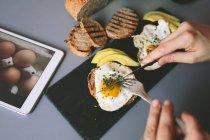 Vista potata delle mani umane taglio uovo fritto — Foto stock