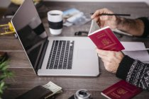 Man holding passport at table with laptop — Stock Photo