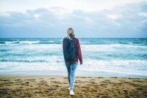 Молодая женщина, ходить на берегу пляжа в зимний период — стоковое фото