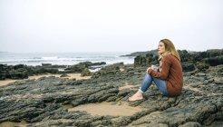 Einsame Frau sitzt im Winter auf Felsen am Strand — Stockfoto