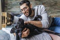 Ritratto di uomo accarezzando cane nero — Foto stock