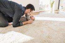 Padre e figlio bambino che giocano sul tappeto a casa — Foto stock