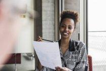 Mujer celebración de documento y hablando con el colega - foto de stock