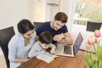 Сім'ї з ноутбук та Путівника планування відпустки вдома — стокове фото