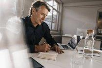 Empresário escrevendo em notebook — Fotografia de Stock