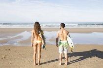 Вид сзади пару серферов с доски для серфинга на пляже — стоковое фото