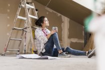 Portrait of young woman sitting by ladder with cup — Stock Photo