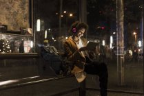 Young woman with headphones and tablet sitting at tram stop — Stock Photo