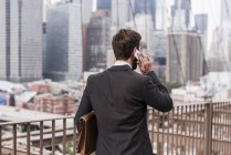 USA, New York, Brooklyn bridge, Rear view of young businessman on phone, cityscape on background — Stock Photo