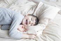 Щасливий хлопець лежав у ліжку з закритими очима — стокове фото