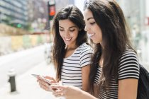 Portrait of two young women using smartphones — Stock Photo