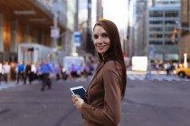 Joven empresaria con smartphone en la calle, de la ciudad Manhattan, en Nueva York, nos - foto de stock