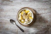Vista superior de flocos de aveia com banana fatiada e iogurte na tigela — Fotografia de Stock