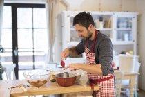 L'homme debout dans la cuisine et de cuisson gâteau anneau — Photo de stock