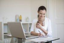 Mãe de freelancer com o bebé no sling, trabalhando em casa, escritório — Fotografia de Stock