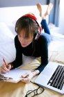 Frau am Bett liegen und schreiben in Zwischenablage — Stockfoto