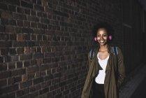 Giovane donna sorridente davanti al muro di mattoni, ascolto musica con le cuffie — Foto stock