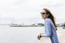 Young woman standing in Manhattan, looking at river — Stock Photo