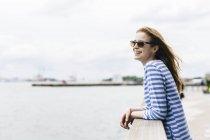 Junge Frau stehend in Manhattan, mit Blick auf Fluss — Stockfoto