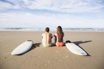 Задній вид серферів пара, сидячи на пляжі з дошки для серфінгу, дивляться на se — стокове фото