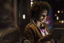Junge Frau mit Kopfhörern mit Tablette während der Wartezeit an der Straßenbahnhaltestelle — Stockfoto