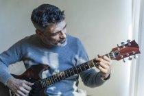 Porträt eines reifen Mannes, der Gitarre spielt — Stockfoto
