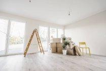 Scatole mobili e scala nella stanza vuota della nuova casa — Foto stock