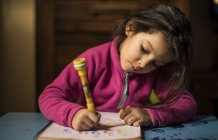 Drawing little girl at home — Stock Photo
