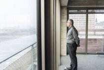 Businessman looking out of window — Stock Photo