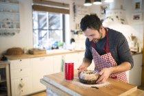 Man standing in kitchen and garnishing ring cake — Stock Photo