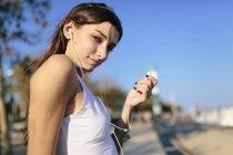 Портрет молодой женщины, держащей наушник и смотрящей в камеру — стоковое фото