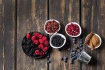 Verschiedene Beeren und Samen in Schalen auf hölzernen Hintergrund — Stockfoto