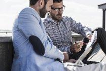 Двоє бізнесменів блокнота і планшетного ПК, які працюють на відкритому повітрі — стокове фото