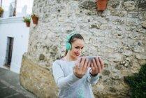 Young woman weith headphones taking selfie — Stock Photo