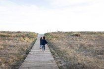 Rear portrait of two boys running away on wooden footpath in field — Stock Photo
