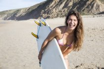 Young laughing woman with surfboard at sandy beach in sunny weather — Stock Photo