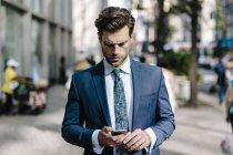 Portrait d'un homme d'affaires utilisant un smartphone dans la rue — Photo de stock