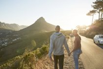 South Africa, Cape Town, young couple walking hand in hand at roadside — Stock Photo