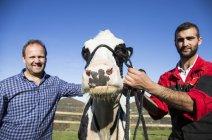 Portrait de deux agriculteurs avec la vache à la ferme — Photo de stock