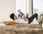 Father playing with baby son, lying on carpet — Stock Photo