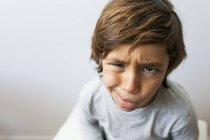 Retrato de niño tirando de la cara y mirando a la cámara - foto de stock