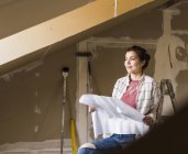 Portrait of young woman holding construction plan — Stock Photo