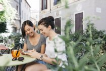 Italy, Padua, two young women checking cell phones at sidewalk cafe — Stock Photo