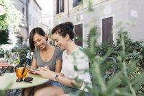 Италия, Падуя, две молодые женщины, проверка мобильные телефоны на тротуаре кафе — стоковое фото