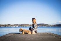 Femme avec chien sur la jetée, marine sur fond — Photo de stock