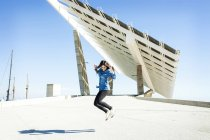 Woman jumping in air with solar panels — Stock Photo